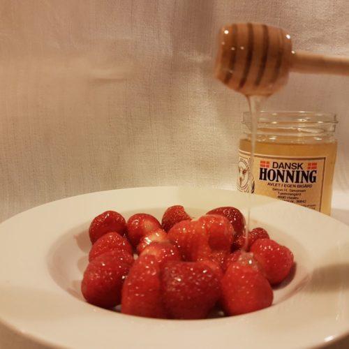 Skål med nye jordbær med dansk honning produceret af Tuemosegård