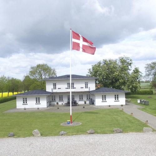 Hvid villa med Danmarks flag i forgrunden. Gule marker på højre side og grønt græs. Vingård.