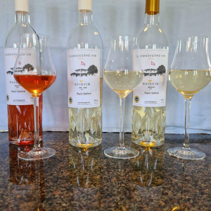 Rødvin, hvidvin og rosévin med vinglad på et bord